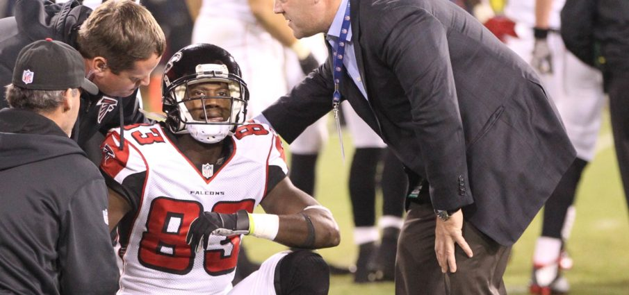 Dr. Spero Karas, head team physician for the Atlanta Falcons on the field with Falcons player