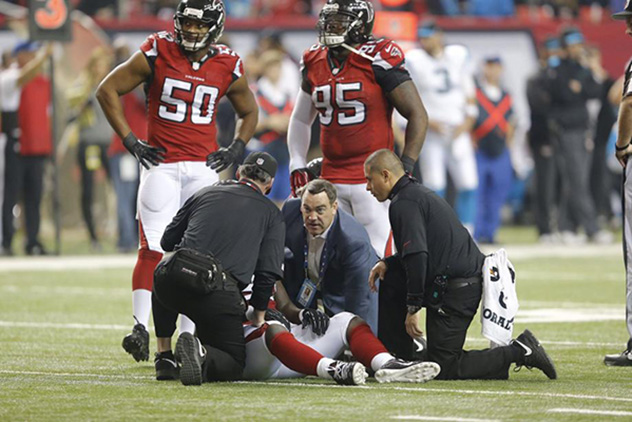 Dr. Spero Karas on the field with injured Atlanta Falcons player